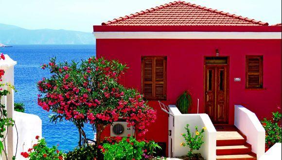 Coastal red house with  colorful flowers. Nimborio