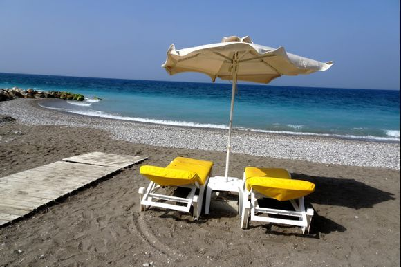 Empty beach with umbrella and chairs, Kritika