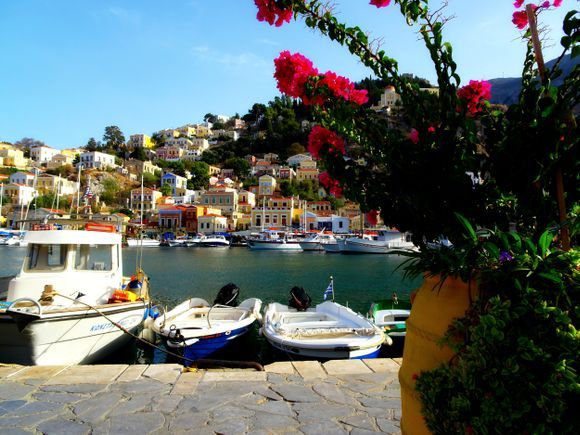 Waterfront with pot of flowers, neoclassical houses and small boats