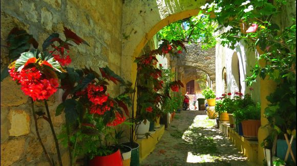 Old town alley with arches and flowers