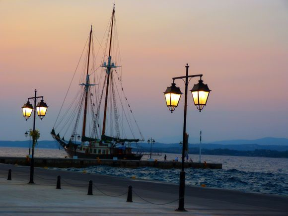 Old harbour with sailboat and lamp posts
