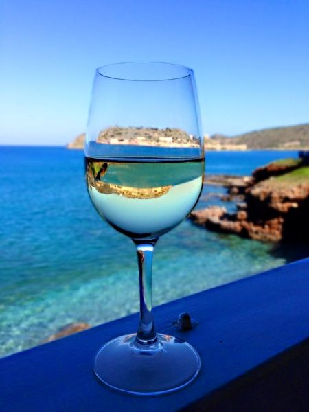 A day without wine is like a day without sunshine. An alternative view of Spinalonga. By Mikki Lee