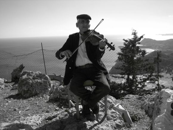 an old poor guy with a violin, playing to survive