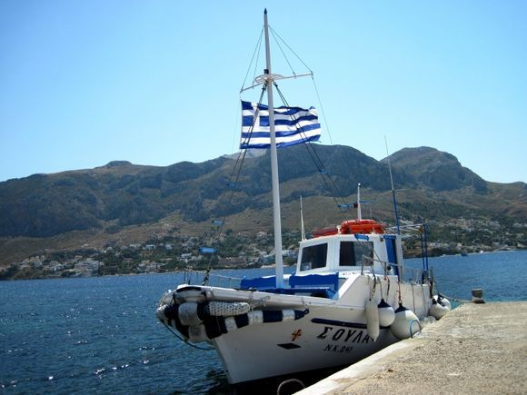Telendos island, a boat in the harbour of the small island, in the background the island of Kalymnos