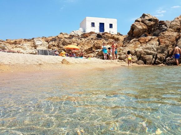 Mykonos august 2017, Agrari and Elia are located near each other, forming a huge sandy beach, 10 kilometres from the island's capital. Agrari Beach is less popular than its neighbor Elia and much calmer. They both can be reached by local bus and by taxi-boat. As with many of the beaches you approach from on high and then down a long, thin, steep road. There is a smallish cafeteria and two sets of beach loungers with shades. There are many nudists on this beach. From this beach you can walk over the rocks to the left to visit Elia beach.