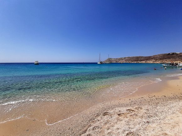 Mykonos July 2021, Elia is a big sandy beach, located 12 kilometers from the capital. Elia is the longest sandy beach of Mykonos, fully organized, offering a wide choice of taverns and bars as well as water sports facilities such as water-skiing, parasailing, and windsurfing.