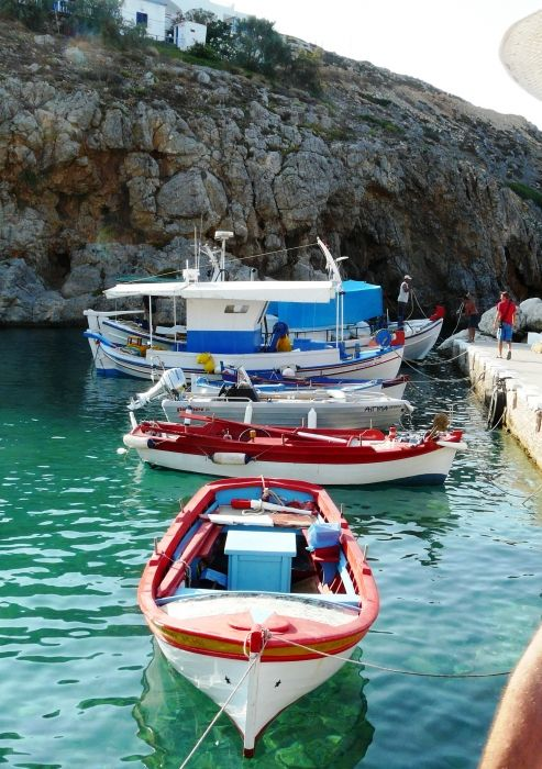 Colourful fishing boats sit in the crystal clear water at the tiny port on Antikythira, a small island off of Kythira.